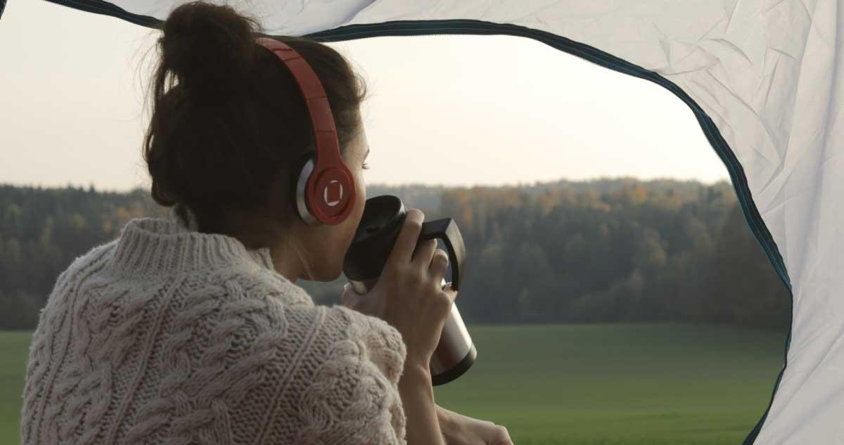 屋外テント内でヘッドホンをつけている女性のイメージ画像