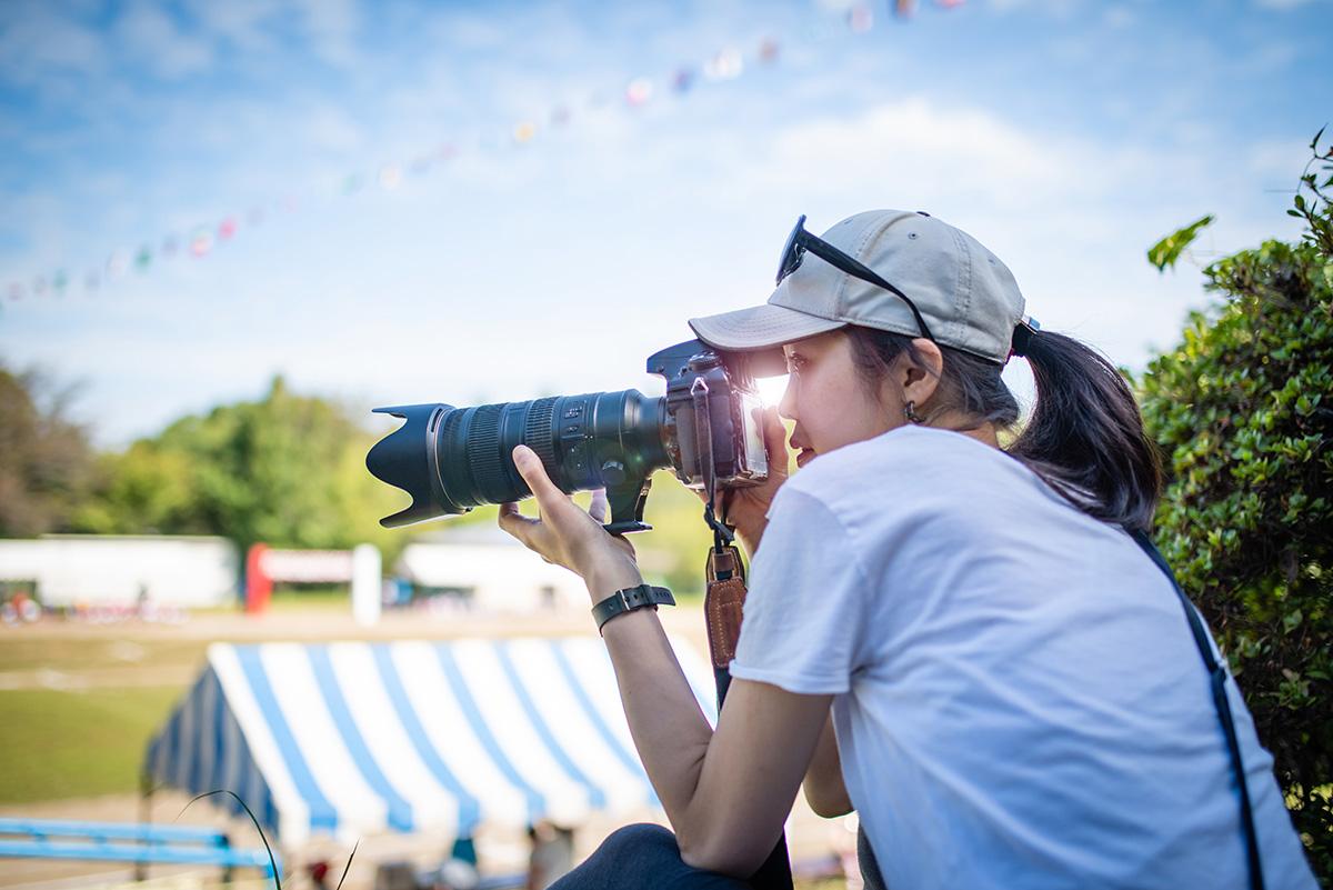 デジタル一眼レフカメラで運動会の様子を撮影している女性のイメージ画像