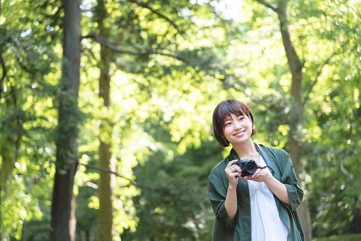 新緑の中、女性がデジタル一眼レフカメラを持って撮影しているイメージ画像