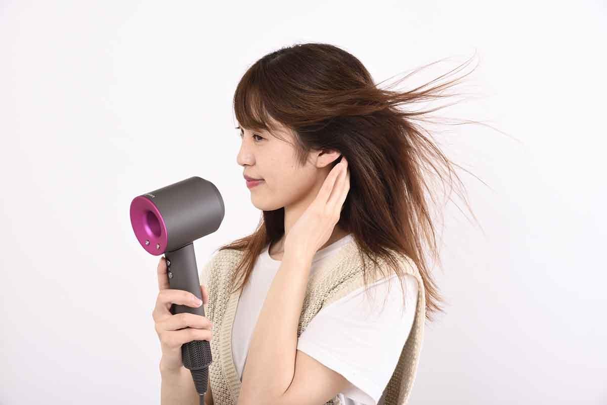 女性がヘアドライヤーを使用しているイメージ画像